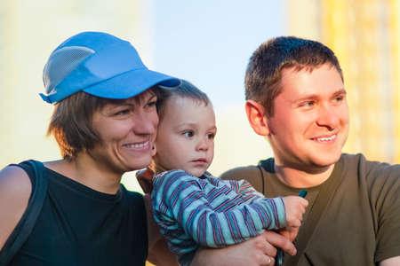 Ritratto di giovane famiglia caucasica di tre insieme all'aperto. Immagine orizzontale