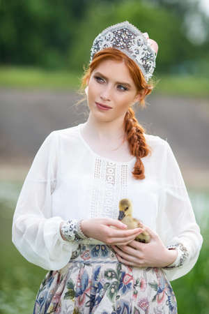 Fashion Portrait of  Gorgeous Young Caucasian Female Posing With Duckling in Russian Style Dress and  Kokoshnik Outdoors. Vertical image Composition