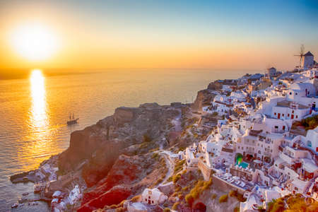 Beautiful Tranquil Cityscape of Oia Village in Santorini Island Before the Sunset. Lonely Sailing Boat Floating On Background. Horizontal  Shot 免版税图像