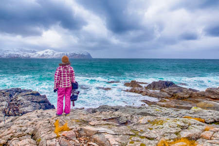 Female Photographer with Gear Standing on Rock In Front of Snowy Mountains in Lofoten Islands in Norway. Horizontal Image