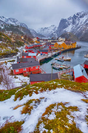 Traditional Norwegian Village in Nusfjord in Lofoten Islands in Norway. Against High Mountains. Vertical Image Composition