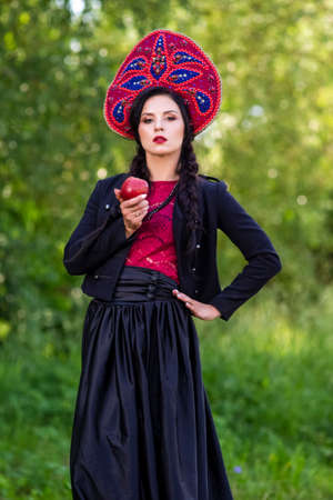 Fashion Brunete Woman In Russian Style Kokoshnik Outdoors Against Nature Background. Posing With Apple.Vertical Shot Stock Photo
