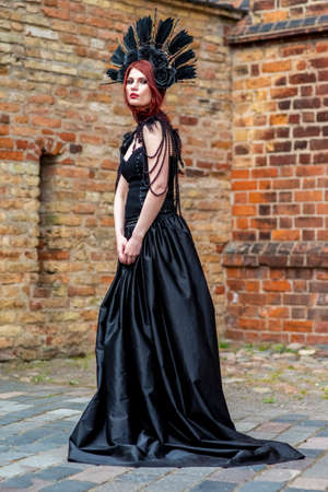 Gothic Woman in Black Dress and Feather Crown.Against Brick Wall Outdoors. Vertical Image Banco de Imagens