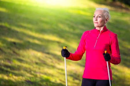 Closeup Portrait of Smiling Sportive Senior Woman Doing Nordic Walking in Park. Horizontal image Composition