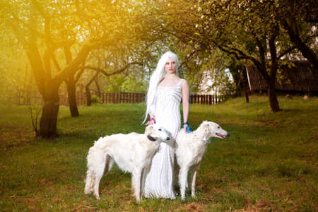 Female Elf with Long White Hair Holding A Pair of Greyhounds in Forest Outdoors.Posing Against Sunglight. Horizontal Image