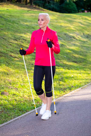 Portrait of Smiling Sportive Senior Woman Doing Nordic Walking in Park. Vertical Image Composition