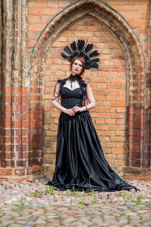 Portrait of Gothic Caucasian Woman in Black Dress. Wearing Artistic Feather Crown. Posing Against Old Castle Gates. Vertical Image Composition