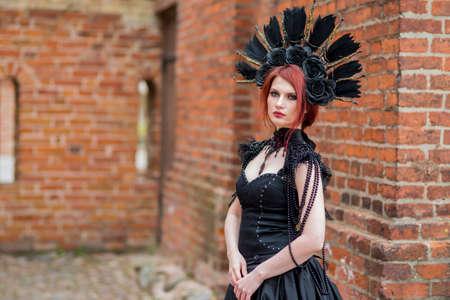 Portrait of Gothic Caucasian Woman in Black Dress and Artistic Feather Crown. posing Against Old Castle Gates. Horizontal Image Composition Banco de Imagens