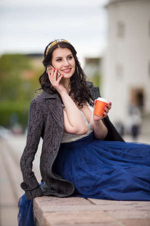 Caucasian Brunette Woman Drinking Coffee In The City Center and Speaking on Cellphone.Vertical Image