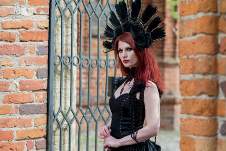 Portrait of Gothic Caucasian Woman in Black Dress and Artistic Feather Crown. posing Against Old Castle Gates. Horizontal Image