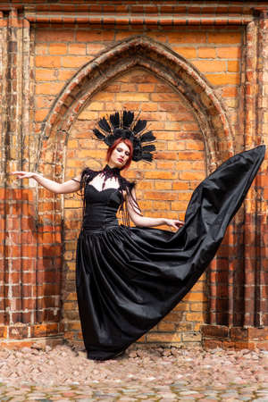 Portrait of Gothic Woman in Black Flying Dress. Wearing Artistic Feather Crown. Posing Against Old Castle Gates. Vertical Image Composition Banco de Imagens