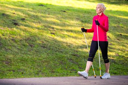 Porträt der lächelnden sportlichen älteren Frau, die Nordic Walking im Park macht. Horizontale Bildzusammensetzung Standard-Bild