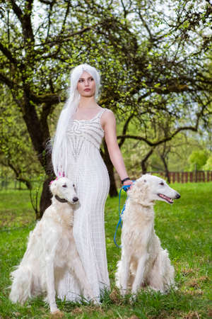Female Elf with Long White Hair Holding A Pair of Greyhounds in Forest Outdoors.Posing Against Nature. Vertical Image