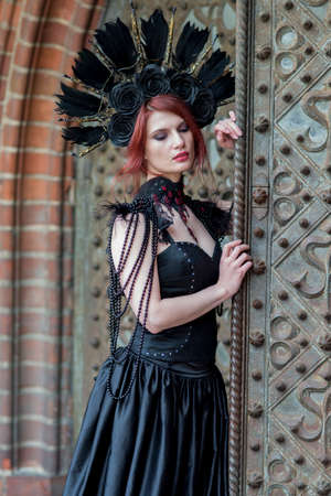 Close-up Portrait of Gothic Girl in Long Black Dress. Wearing Artistic Feather Crown with Roses. Posing Against Old Castle Gates. Vertical Image Composition