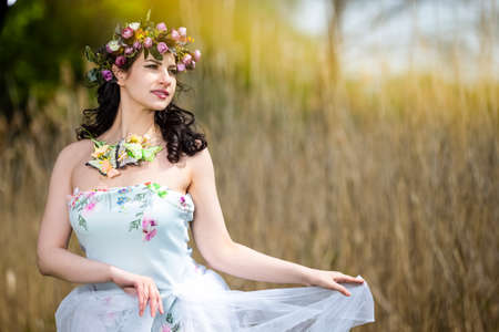 Beautiful Portrait of Caucasian Brunette Lady with Unique Flowery Chaplet and Butterflies. Posing Against Nature Background.Horizontal Image
