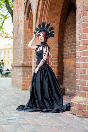 Portrait of Tranquil Gothic Girl in Long Black Dress. Wearing Artistic Feather Crown with Roses. Posing Against Old Castle Gates. Vertical Shot