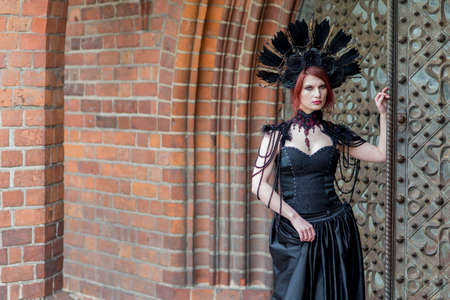 Gothic Girl in Long Black Dress. Wearing Artistic Feather Crown with Roses. Posing Against Old Castle Gates. Horizontal Image Composition