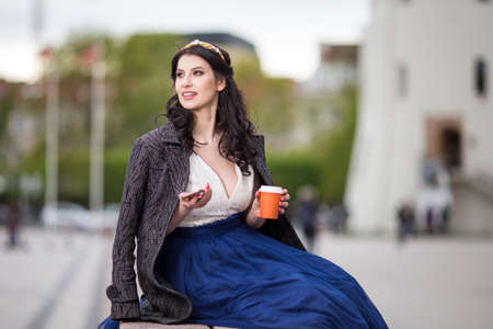 Caucasian Brunette Woman Drinking Tea or Coffee In The City Center Outdoors. Horizontal Image