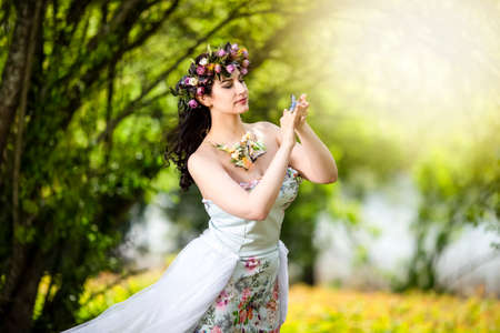Fantastic Portrait of Sensual Brunette Female in White Dress Outdoors. Posing with Flowery Chaplet and Butterfly Against Sunlight. Horizontal image