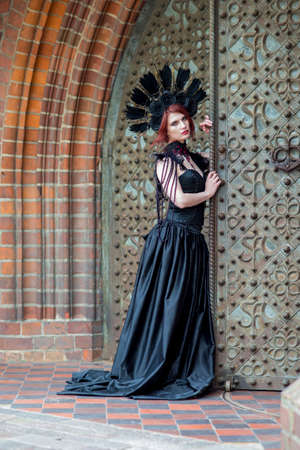 Gothic Girl in Long Black Dress. Wearing Artistic Feather Crown with Roses. Posing Against Old Castle Gates. Vertical Orientation