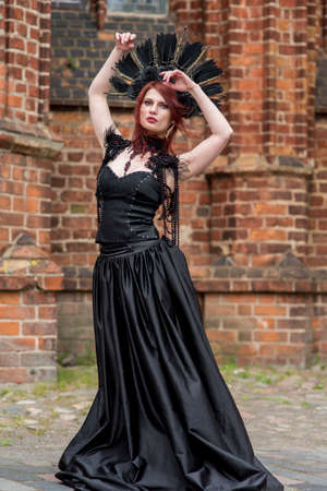 Gothic Woman in Black Dress and Feather Crown.Against Brick Wall Outdoors. Posing with Lifted Hands. Vertical Image