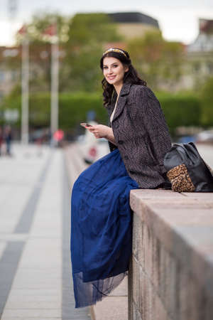 Portrait of Beautiful Smiling Woman With Cellphone Outdoors. Vertical image Stock fotó