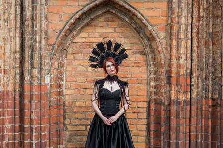 Portrait of Gothic Woman in Black Long Dress. Wearing Artistic Feather Crown. Posing Against Old Castle Gates. Horizontal Image Composition