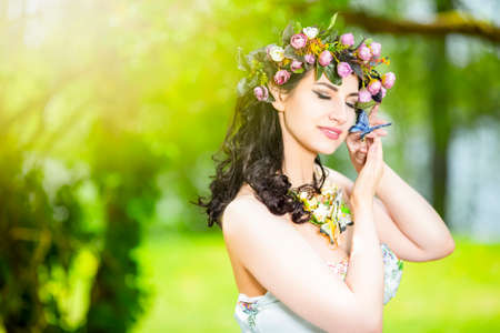 Portrait Sensual Dreaming Brunette Female in White Dress Outdoors. Posing with Flowery Chaplet and Butterfly Against Sunlight. Horizontal Image Composition Banco de Imagens