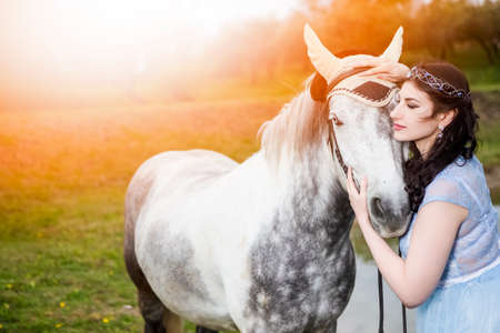 Sensual Caucasian Brunette With Tiara Embracing with High Breed Horse Outdoors.against Bright Light on Background. Horizontal Image Foto de archivo