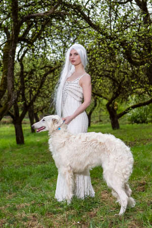 Long-Haired Elf Woman in White Dress Walking White Greyhound in Forest. Vertical image Composition