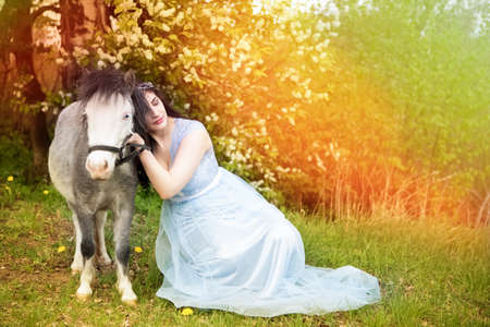 Gorgeous Portrait of Sensual Caucasian Brunette in Long Blue Dress Posing With pony Horse Against Bright Light.Horizontal image