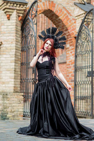 Portrait of Gothic Caucasian Woman in Black Dress and Artistic Feather Crown. posing Against Old Castle Gates. Vertical Image Banco de Imagens
