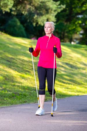 Full Length Portrait of Positive Sportive Senior Woman Doing Nordic Walking in Park. Vertical image Composition