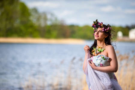 Gorgeous Caucasian Brunette Woman in Decorated Dress and Flowery Chaplet with Butterflies. Posing Against Nature Background. Horizontal Image