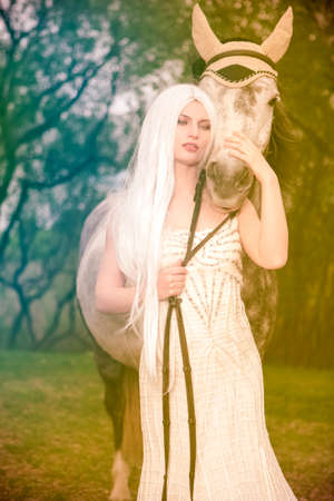 Gentle Dreaming Caucasian Blond Female with Long Hair Standing with Grey Horse Against Bright Light on The Background. Vertical Image