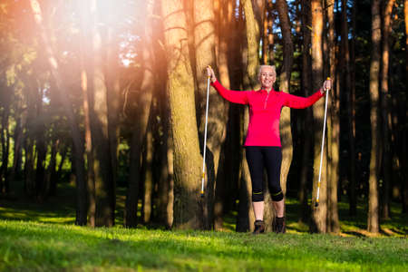 Happy Exclaiming Senior Caucasian Woman Having Nordic Treckking Exercises Outdoors in Forest. Horizontal Image