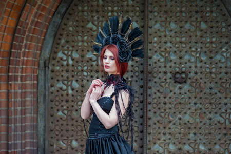 Fashionable Gothic Woman in Long Black Dress. Wearing Artistic Feather Crown. Posing Against Old Castle Gates. Horizontal Shot