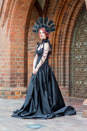 Portrait of Tranquil Gothic Girl in Long Black Dress. Wearing Artistic Feather Crown with Roses. Posing Against Old Castle Gates. Vertical Image Composition