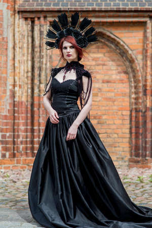 Fashionable Gothic Woman in Long Black Dress. Wearing Artistic Feather Crown. Posing Against Old Castle Gates. Vertical Image