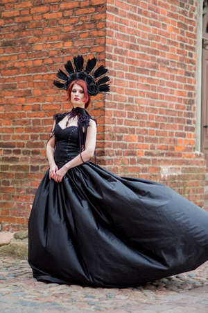 Portrait of Gothic Caucasian Woman in Black Flying Dress. Wearing Artistic Feather Crown. Posing Against Old Castle Gates. Vertical Image Composition Banco de Imagens