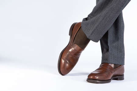 Closeup of Crossed Mens Legs Wearing Brown penny Loafers. Against White Background. Horizontal image