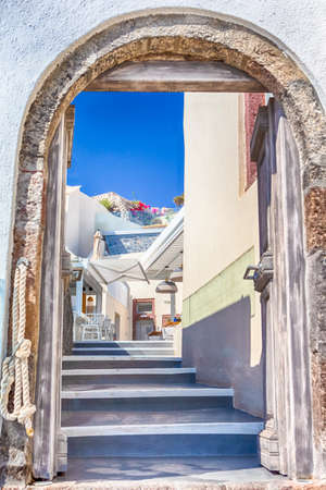 Open terrace In One of the Comfortable and Coziest Corners of Thira City of Santorini island in Greece.Naturally Framed with Entrance Gates. Vertical image.