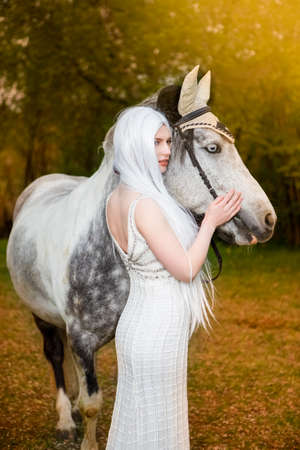 Sensual and Sexy Caucasian Blond Female with Long White Hair Standing with Horse Against Bright Light on The Background.Vertical image Orienation