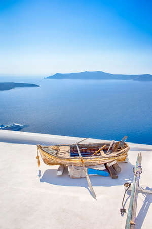 Old Wooden Boat on White roof in Thira Against The Aegean Sea and The Chain of Islands in Santorini. Vertical Image