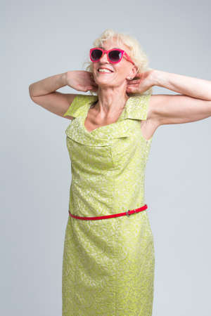 Happy Extravagant Mature Caucasian Blond Woman in Red Sunglasses Posing in Green Dress with Hands Lifted and Folded Behind. Vertical Image Composition