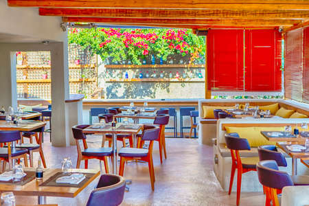 Alluring and Tempting Empty Cafe in Thira at Hot Daytime with Nobody Inside. Horizontal Image