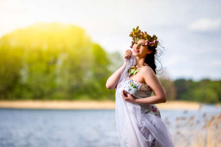 Gorgeous Caucasian Brunette Woman in Decorated Dress and Flowery Chaplet with Butterflies. Posing Against Bright Sunlight. horizontal Image Composition