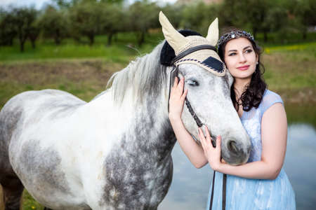 Caucasian Brunette With Tiara Walking with Horse Outdoors. Against Nature Background. Horizontal Image