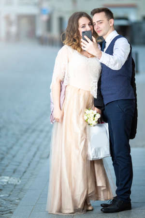 Happy Just Married Caucasian Couple Making Selfie Outdoors in City. Vertical Image Фото со стока