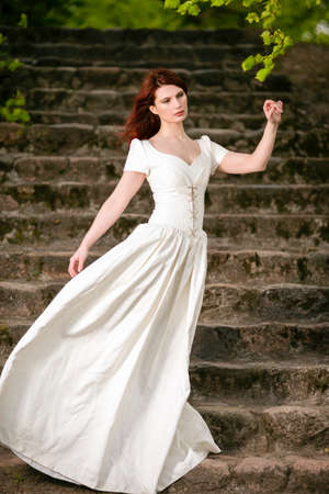 Caucasian Female i  Long White Dress Posing Outdoors on Stairs. Vertical Image Composition